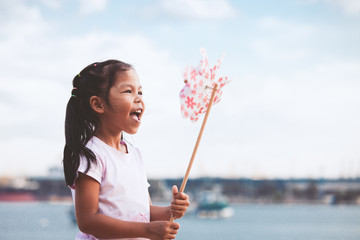 Cute asian child girl playing with toy wind turbine in the beach with happiness