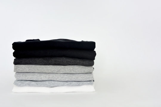 stack of folded black, grey and white color (monochrome) t-shirt on white background, copy space