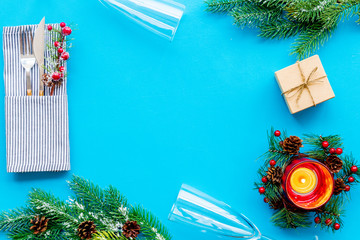 Christmas and new year decoration with gift, plate and fir tree blue table background top view space for text
