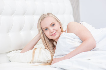 Young sexy blond woman resting on the bed