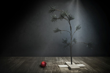 Small Sparse Christmas Tree with red ornament on the floor