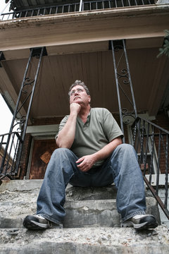 Middle aged man sitting on the steps of a house in the inner city