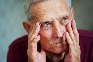 Age-related dementia. Health problems in age. Sad elderly european man holding his head. Migraine