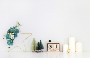 Christmas interior, candles, decorative Christmas trees, Christmas wreath in the shape of a star decorated with eucalyptus branches.