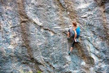 The climber is training to climb the rock.