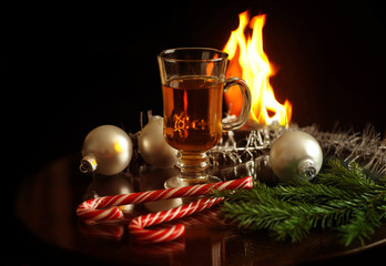 Hot drink in a glass, white Christmas balls, fir branches and sweets on a fireplace fire background. New Year and Christmas card.