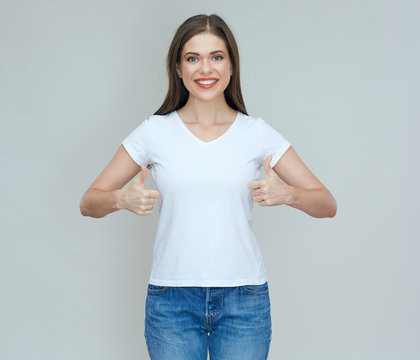 Smiling woman wearing casual white t shirt doing thumb up.