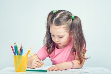 beautiful cute little girl drawing picture on white paper with colorful pencils