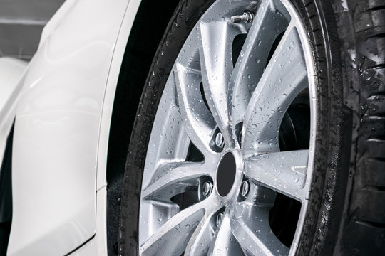 Cars in a carwash. Car wash with foam in car wash station. Carwash. Washing car wheel at the station. Car washing concept.