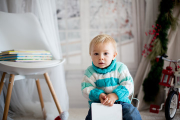 Cute little toddler child with colorful book at home on a snowy winter day