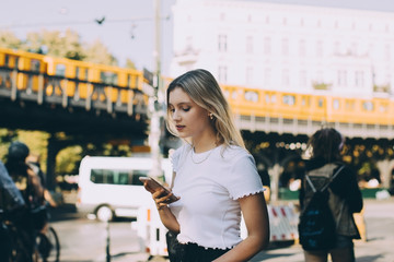Young woman using mobile phone while walking by street in city