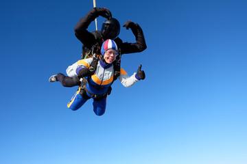 Acrylic Prints Sky sports Tandem skydiving. Girl-passenger is having fun in the sky.