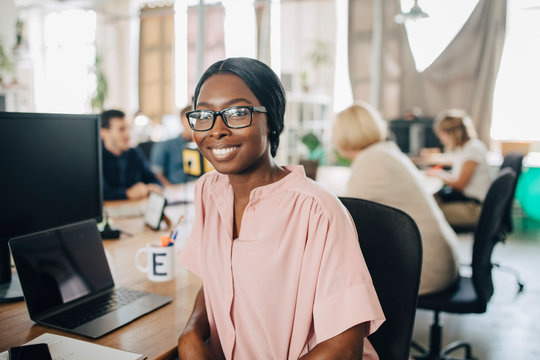 Portrait of smiling young businesswoman sitting at desk in creative office