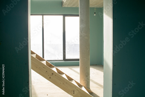 The interior of the unfinished house, with a ladder and ...
