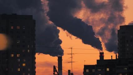 Fotobehang - Smoke pollution from smokestacks over residential buildings city skyline silhouette. 4K UHD Timelapse.