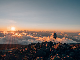 a girl with wanderlust standing on Haleakalā and watching the sunset