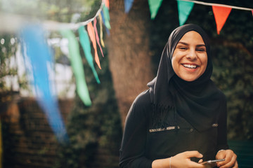 Portrait of smiling young woman in hijab holding mobile phone at backyard