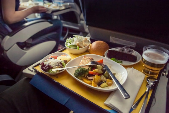 Passenger eats food on Board the plane. Food served on board of business class airplane on the table. Tray of food in the airplane. Tray of food on the plane, business class travel.