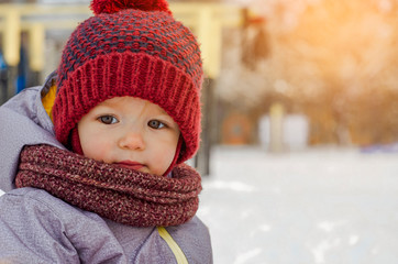 Cute little funny child in colorful winter clothes having fun with snow outdoors. Active outdoors leisure with children in sunny winter
