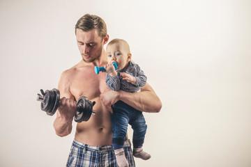 Doing sport. Active family enjoy sport and fitness. Father and child training together. Healthy family lifestyle. Strong man and baby boy with dumbbells. Father and son build muscles, copy space