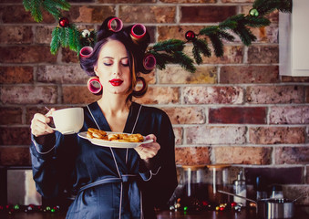 Pregnant housewife in bathrobe cup and cookies at kitchen in Christmas time