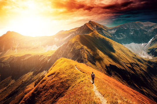 Hiker following the trail on top of mountain range