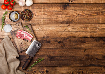 Fresh raw butchers lamb beef cutlets on chopping board with vintage meat hatchet on wooden background.Salt, pepper and oil with tomatoes and garlic and barbeque sauce