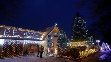 People take pictures in front of a private house decorated with Christmas lighting in the village of Chotovice