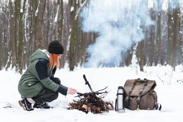 Girl is sitting near camp fire an in winter time. Concept adventure active vacations outdoor. Winter camping. Snowy forest. vintage backpack and thermos with tea, coffee
