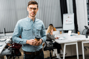 selective focus of young businessman with coffee to go in office with multiracial colleagues behind