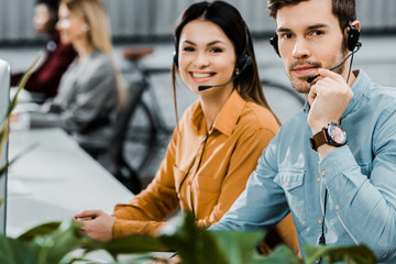 smiling call center operators in headsets looking at camera in office