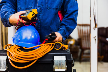 Electrian engineer holding multimeter and tools in hand, standing behind the heavy duty tool box, image including power cord, Blue hard hat (helmet) and gloves.
