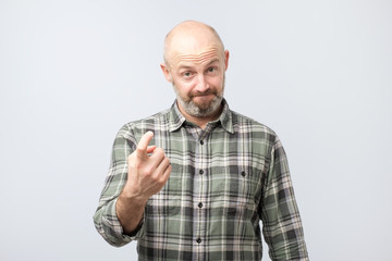 Playful bearded adult showing come here gesture with index finger and smiling over gray background.