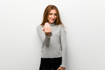 Redhead girl over white wall inviting to come with hand. Happy that you came