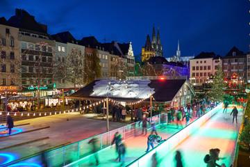 Weihnachtsmarkt in Köln am Heumarkt bei Nacht. Sicht auf die Eisbahn auf der Besucher Schlittschuh laufen können.
