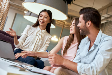 Young couple in a tour agency are listening propose of travel agent