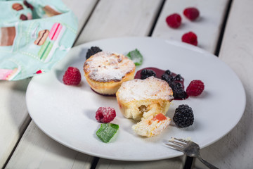 Cottage cheese pancakes, syrniki, curd fritters with fresh berries on white wooden background