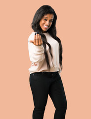 Young afro american woman inviting to come with hand. Happy that you came on isolated brown background