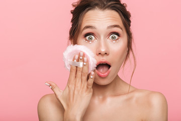 Shocked young woman posing isolated over pink wall background holding powder puff.