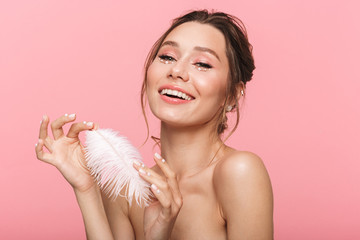Happy cheerful young woman posing isolated over pink wall background holding feather leaf.