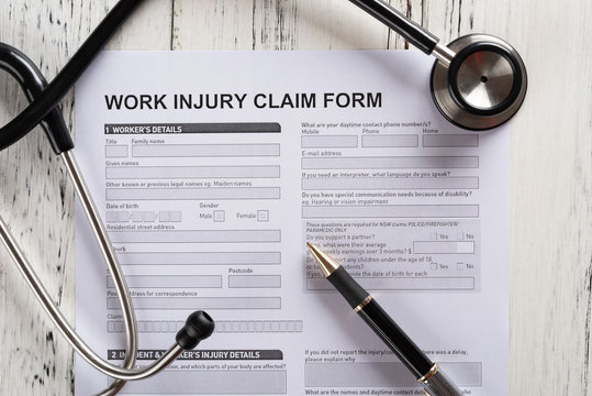 top view work injury claim form with stethoscope  medical and insurance concept