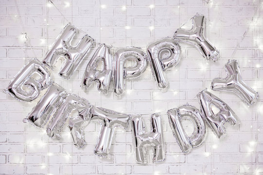 birthday party decoration - happy birthday letters air balloons over brick wall with lights