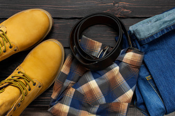 Men's casual wear, yellow work boots from natural nubuck leather, blue jeans, checkered shirt and brown belt on dark wooden background top view flat lay copy space. Trendy casual shoes, youth style.