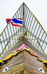 Thai architecture looking like a ship from bottom view with thai national flag.