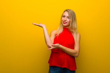 Young girl with red dress over yellow wall extending hands to the side for inviting to come