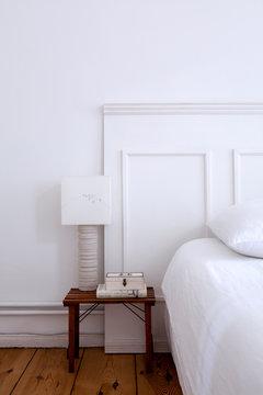 Bett vor weisser Paneelen Wand und Nachtisch mit Lampe