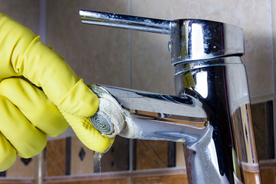 Hand in  yellow glove repairs faucet aerator,  limescale on  tap mixer.