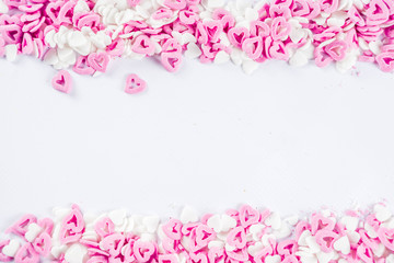 Valentine's sweets background, white background with sugar hearts sweet sprinkles, copy space top view, layout on white
