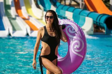 beautiful smiling woman with slim figure in black bikini holding a swim ring posing near the swimming pool and slides. Summer Vacation. Enjoying suntan. Weekend on resort
