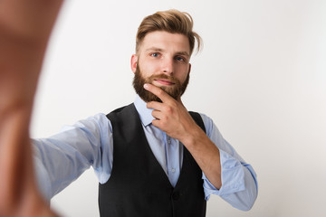 Young bearded man standing isolated over white wall background make selfie by camera.